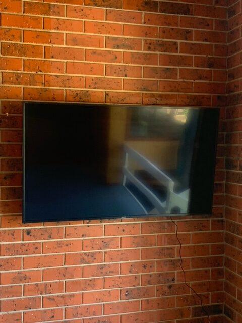 A wall mounted TV on a brick wall